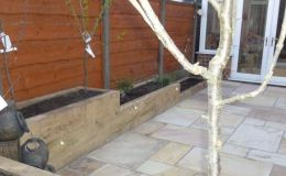 Raised sleeper beds and paving create low maint garden space
